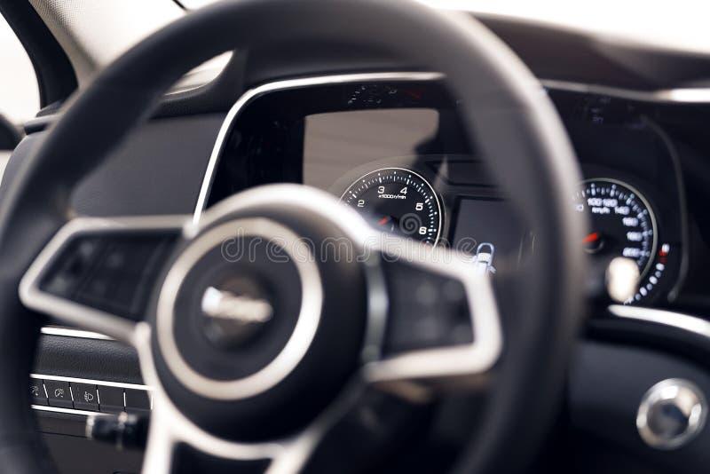 一块现代仪表板的特写镜头在一辆昂贵的汽车的 方向盘被弄脏 免版税库存图片