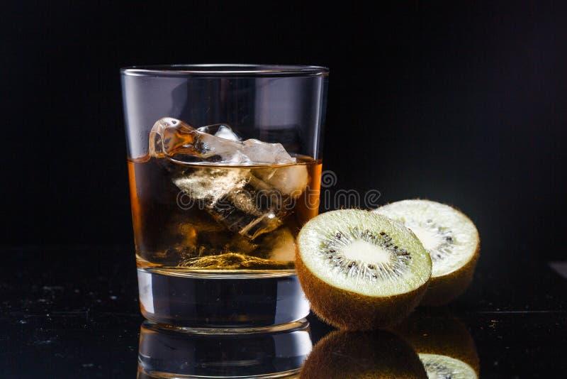 一块玻璃用威士忌酒和冰在背景 免版税库存照片