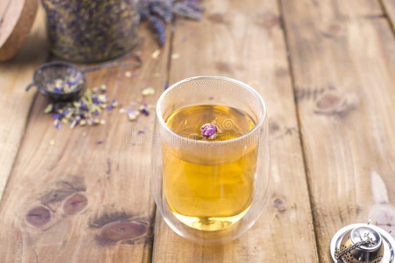 一块玻璃用茶,反弹白花 银行用蜂蜜 在瓶子的干茶 木背景和自由空间文本的,拷贝 库存图片