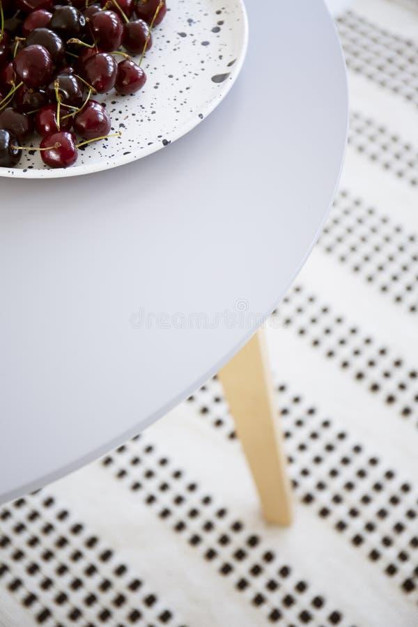 一块白色板材的特写镜头用在一张木餐桌上的樱桃 免版税库存图片