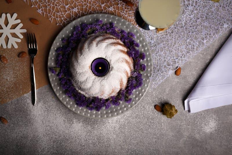 一块白色餐巾,圆环蛋糕的顶视图洒与糖粉末,杏仁,桂香,在五颜六色的光的空泡 免版税库存照片