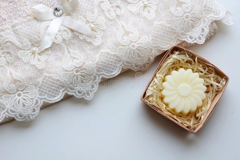 一块米黄毛巾和一块肥皂以一朵花的形式在轻的背景 r 免版税图库摄影