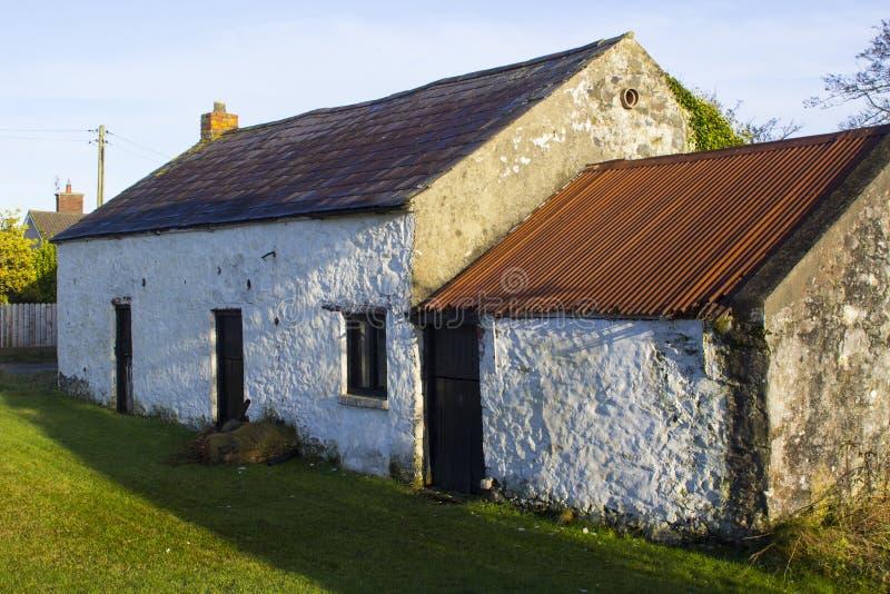 一块老被粉刷的石头修造了与小附录的爱尔兰村庄顶房顶与曼格蓝色瓦和生锈的波纹状的锡s 免版税库存照片