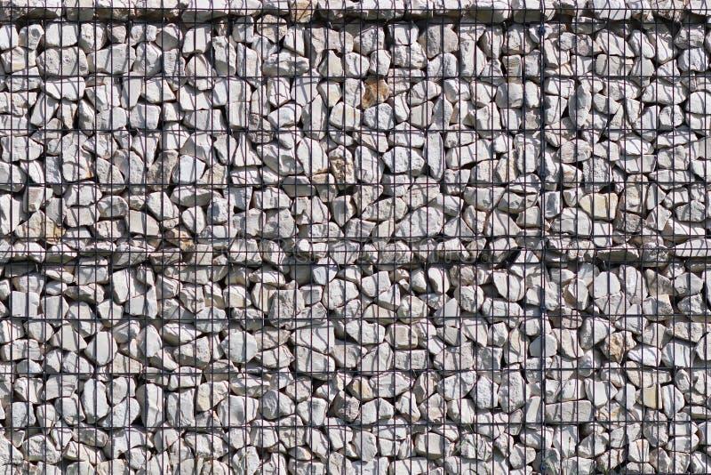 一块自由地说谎的石头的背景的背景的纹理金属滤网支持的 篱芭f的建筑技术  免版税图库摄影