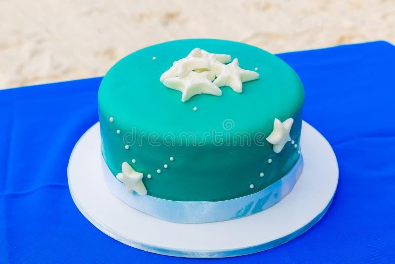 一块蓝色海滩主题的婚宴喜饼装饰了海星 免版税库存图片