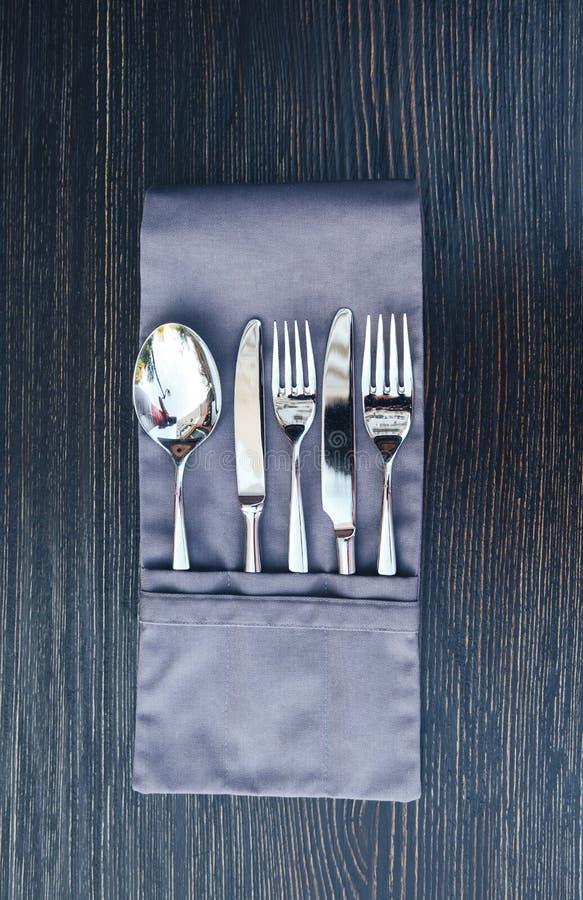一块被折叠的餐巾的特写镜头图象与器物的在木桌上 在木背景的餐巾特写镜头的利器 图库摄影