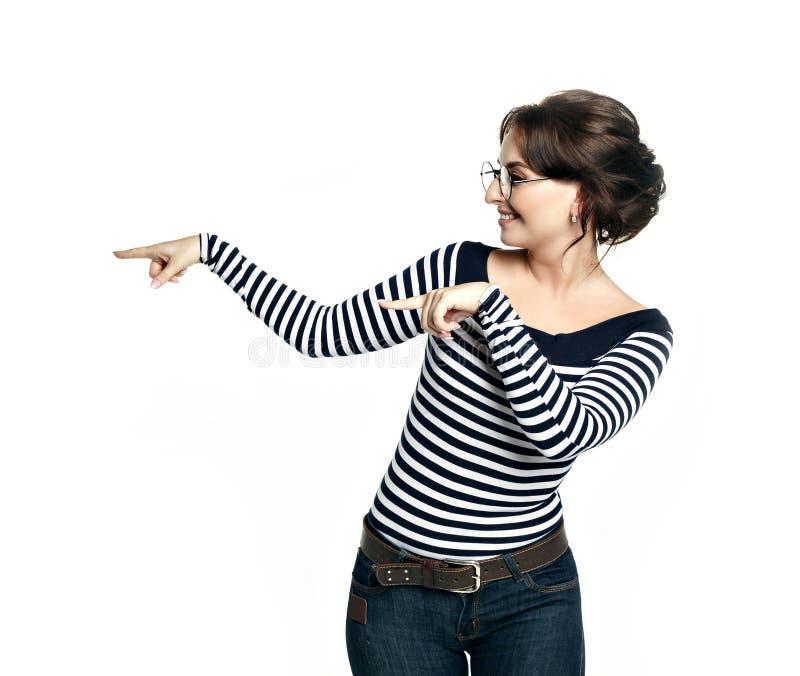 一块镶边紧的女衬衫和圆的玻璃的一个少妇显示与两个手指一个姿态到左边 库存图片