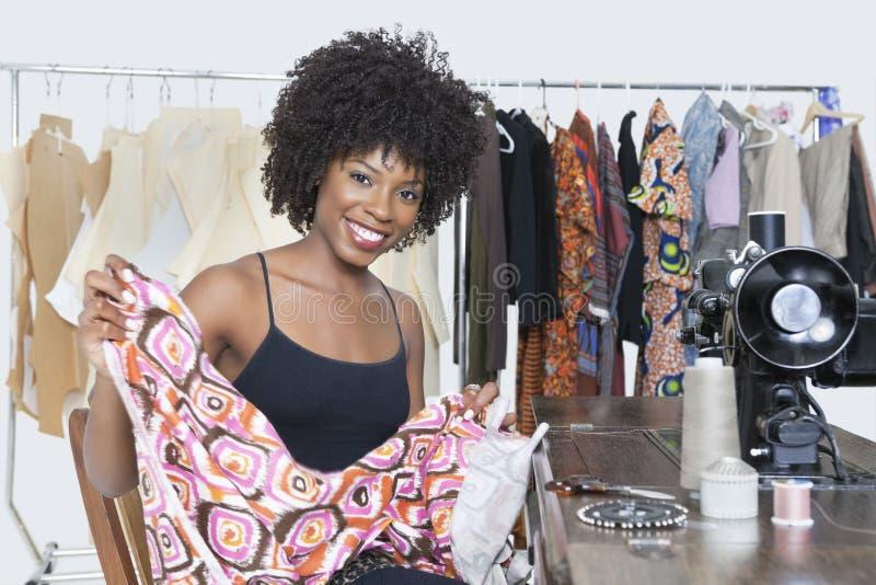 一块非裔美国人的女性时装设计师等待航线布料的画象 库存照片