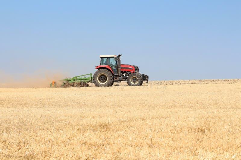 一块麦田的耕种在一台拖拉机的在一个夏天晴天 收获在农业 免版税库存照片