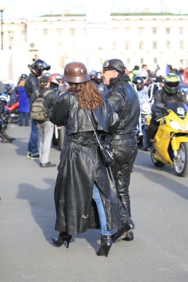 一块黑皮革连衫裤和班丹纳花绸的一个骑自行车的人和他的一件长的黑皮革外套的女性伴侣 活跃,轻微的迷离 免版税图库摄影