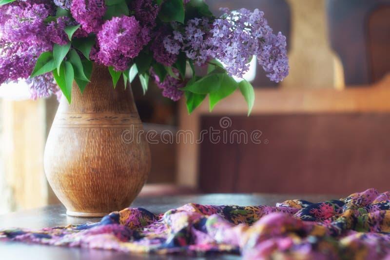 一壶紫丁香花,黑木桌上的丝围巾 库存照片