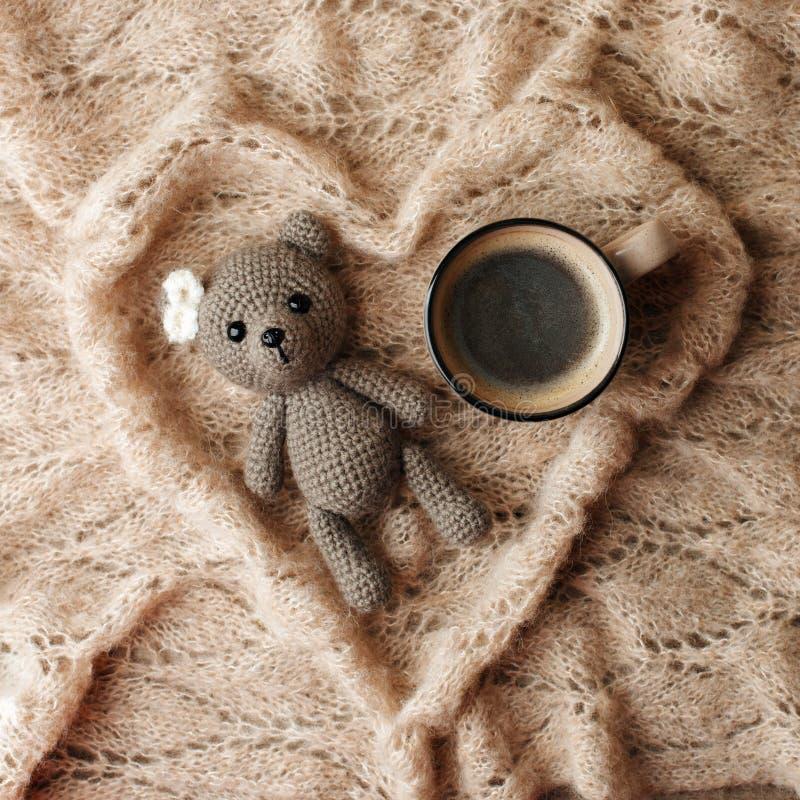 一头小被编织的婴孩玩具熊、咖啡和一条温暖的毯子塑造了在木背景,懒惰困早晨概念的心脏, 免版税库存图片