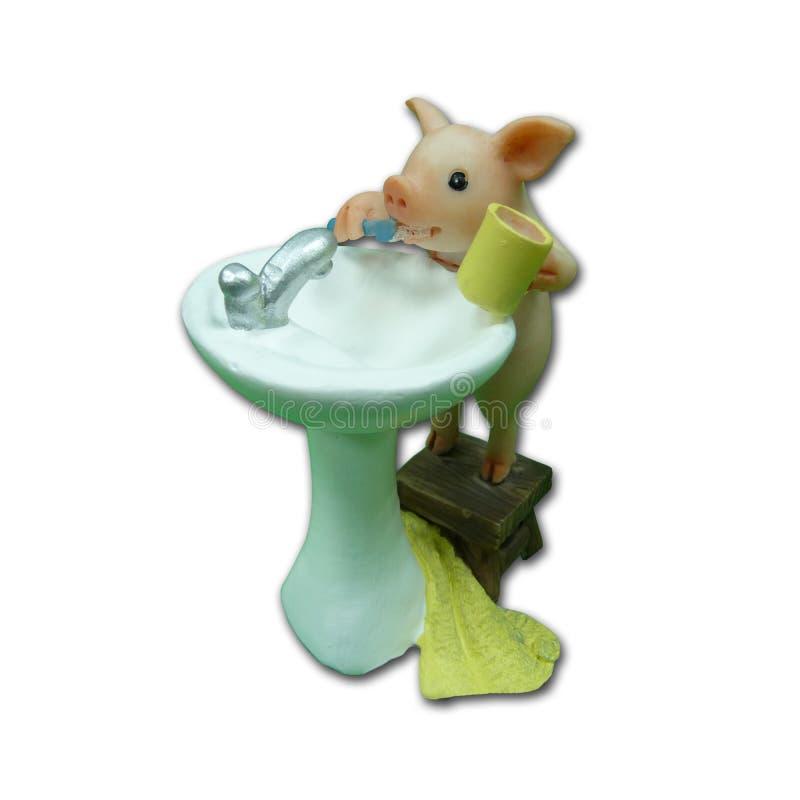 一头桃红色猪在水槽附近掠过他的牙和洗涤 陶瓷雕塑 库存图片