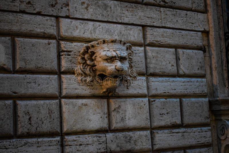 一头狮子的雕象在墙壁上的 免版税库存图片