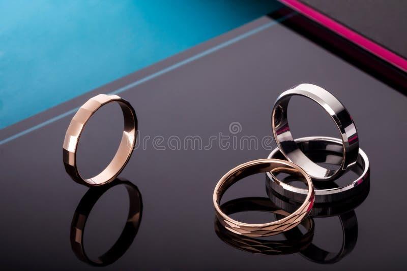 一套与宝石的婚戒 在与反射的时兴的黑光滑的背景 库存图片