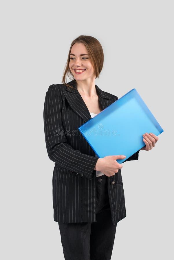 一套严密的黑暗的衣服的年轻成功的妇女与一个蓝色文件夹 免版税库存图片