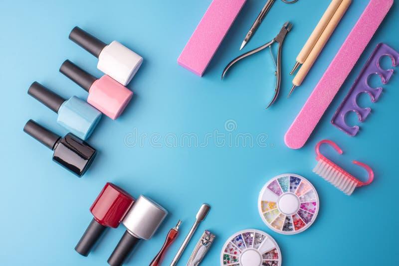 一套为修指甲和修脚的化妆工具在蓝色背景 胶凝体擦亮剂、指甲锉和飞剪机,顶视图 库存照片
