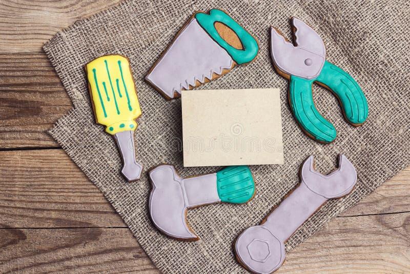 一套以手工具的形式姜饼在与空插件的一张木桌上为文本 人的鲜美创造性的曲奇饼 图库摄影