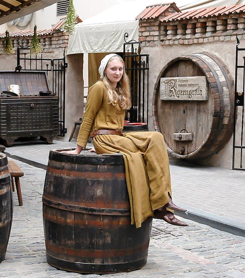 一套全国衣服的女孩坐大桶,做广告是 库存照片
