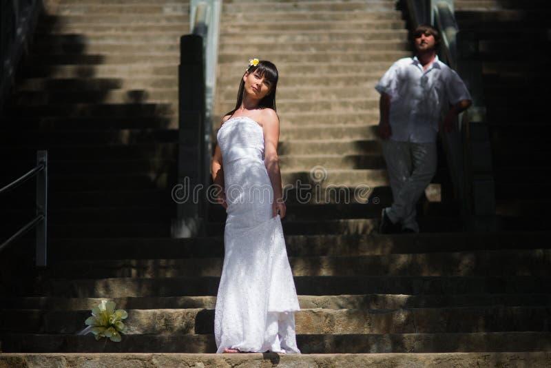 一套典雅的婚礼礼服的新娘在一个大楼梯的背景站立和在她后是白色衣裳的新郎 库存图片