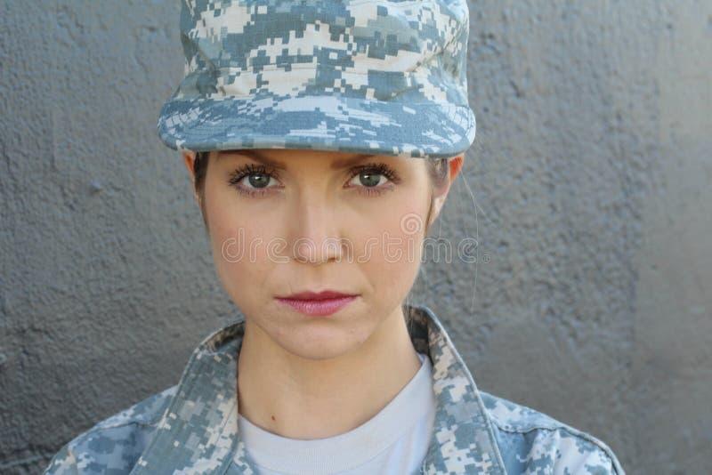一套军用服装的华美的少妇在灰色背景 免版税库存照片