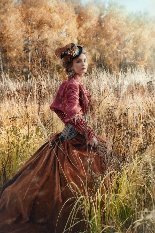 一套历史服装的妇女在秋天森林里 免版税库存照片