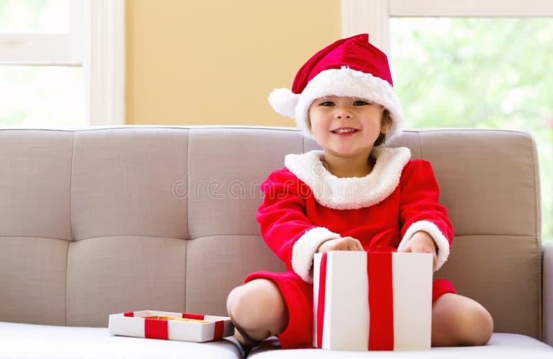 一套圣诞老人服装的愉快的小孩女孩有礼物的 免版税库存照片