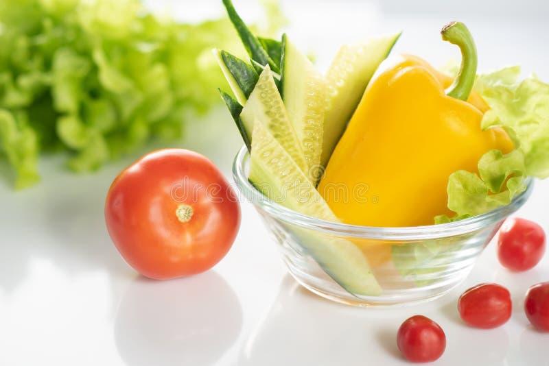 一套在一块白色板材的新鲜蔬菜,菜素食沙拉的准备的 背景是白色的 库存图片