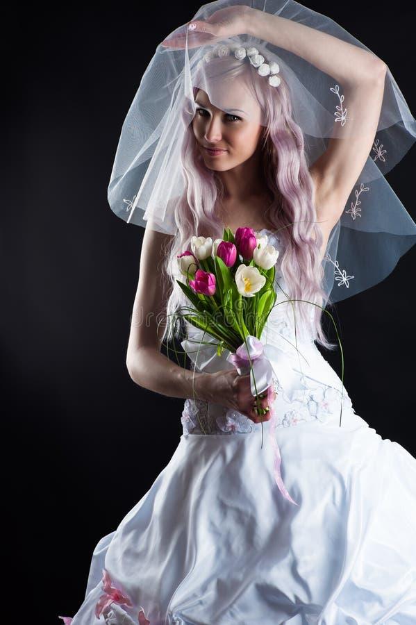 一套婚礼礼服的可爱的妇女与面纱 免版税图库摄影