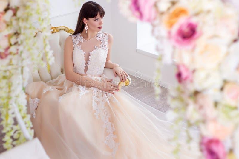 一套婚礼礼服的美丽的新娘在别致的内部在演播室 免版税库存图片
