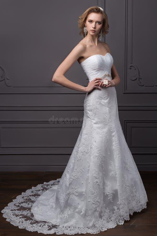 一套婚礼礼服的美丽的柔和的女孩新郎与发型和构成,用花花圈装饰的头发  免版税图库摄影
