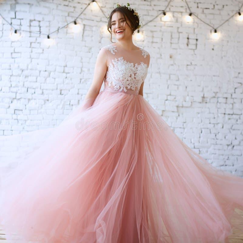 一套嫩浅粉红色的婚礼礼服的新娘在一个早晨 免版税库存照片