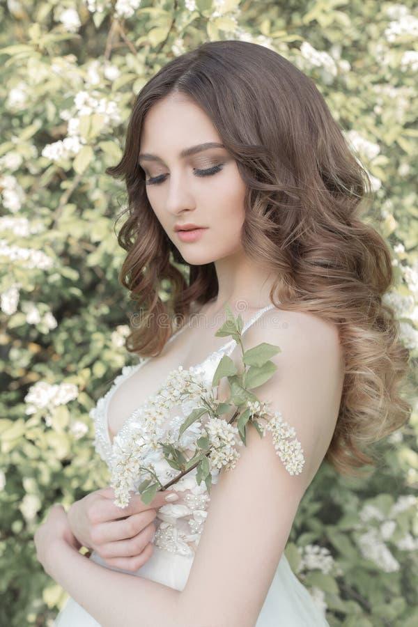 一套嫩空气婚礼礼服的美丽的甜女孩新娘在阳光的一个开花的春天庭院里在日落的 艺术 图库摄影