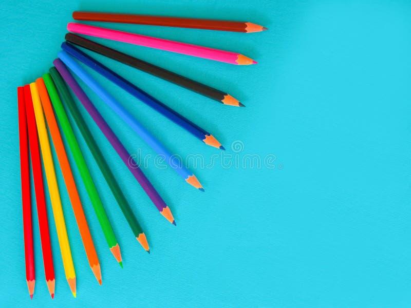 一套孩子的,在绿松石背景的色的铅笔 图库摄影