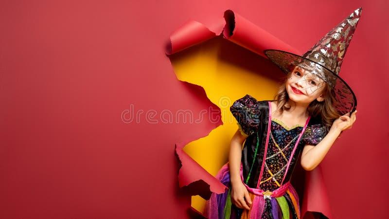 一套巫婆服装的笑的滑稽的儿童女孩在万圣夜 免版税库存图片