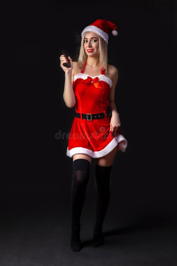 一套性感的红色雪少女服装的年轻美丽的白肤金发的与vape的女孩或圣诞老人项目在手中在黑被隔绝的背景  免版税库存照片