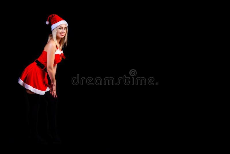 一套性感的红色雪少女服装的年轻美丽的白肤金发的在黑被隔绝的背景的女孩或圣诞老人项目在圣诞节和 免版税库存图片