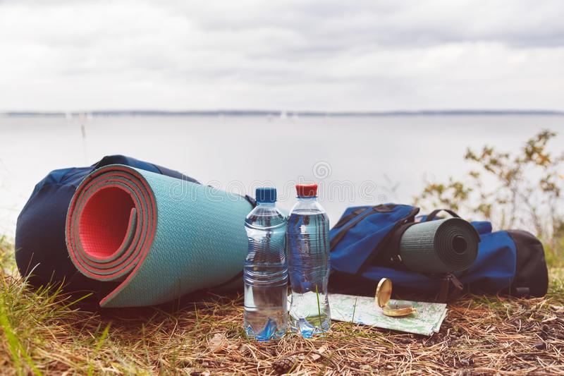 一套旅游辅助部件必要为在狂放的旅游业 被装瓶的水、地毯、背包、地图和指南针  库存图片
