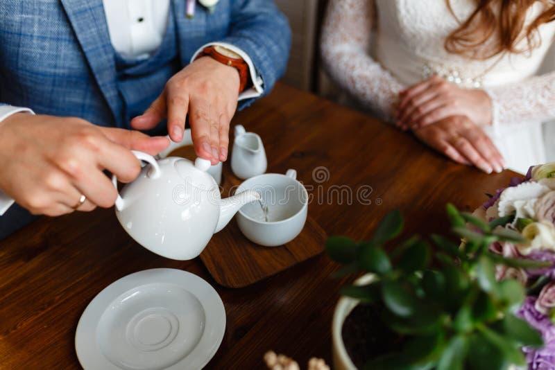 一套时兴的衣服的人倒从一个茶壶的茶在杯子 礼节规则在咖啡馆的 人照顾妇女 一年轻coupl 库存图片