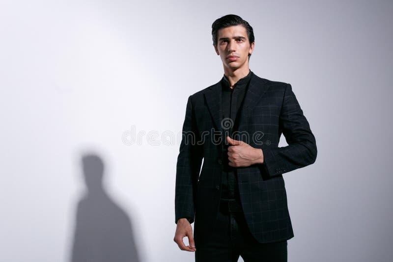一套时髦的衣服的时兴的年轻帅哥,握在验查员夹克的手,隔绝在白色背景 图库摄影