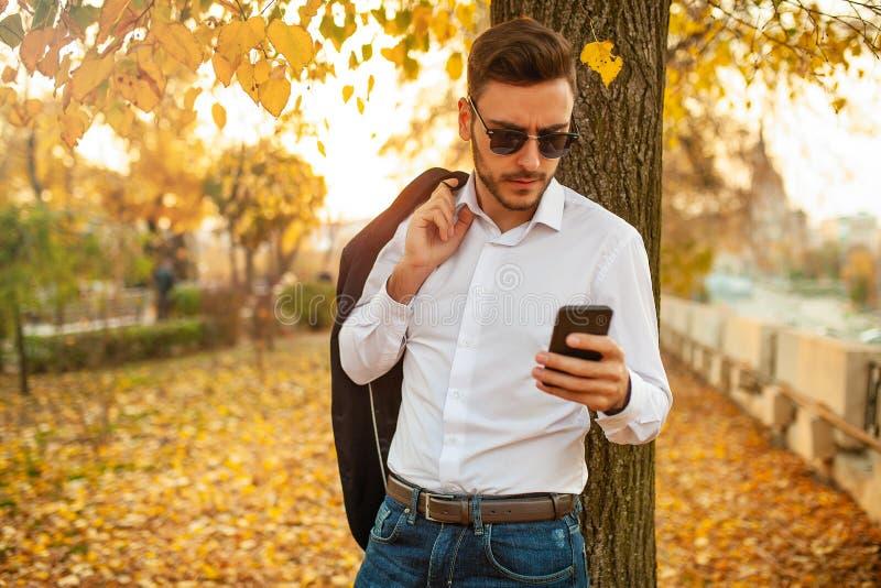 一套时髦的西装和太阳镜的英俊的年轻时兴的人键入消息 免版税库存照片