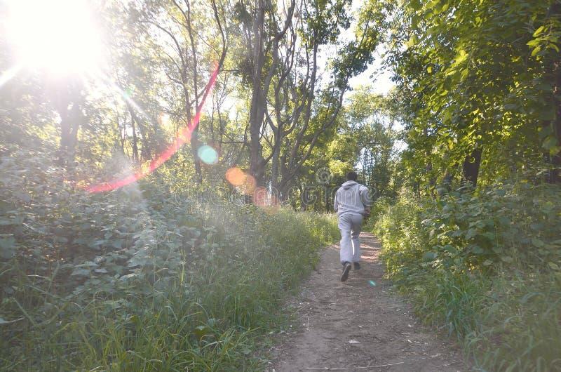 一套灰色体育衣服的一个年轻人沿在中的道路跑 免版税图库摄影