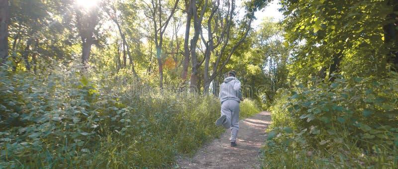 一套灰色体育衣服的一个年轻人沿在中的道路跑 免版税库存图片