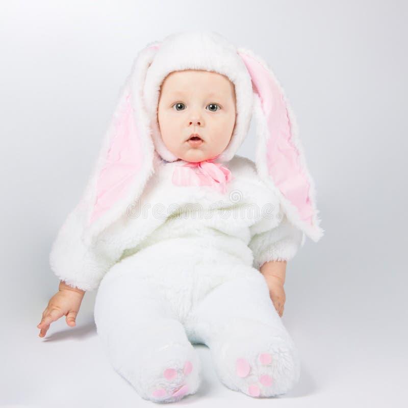 一套白色兔宝宝衣服的小逗人喜爱的婴孩 孩子坐地板 免版税图库摄影