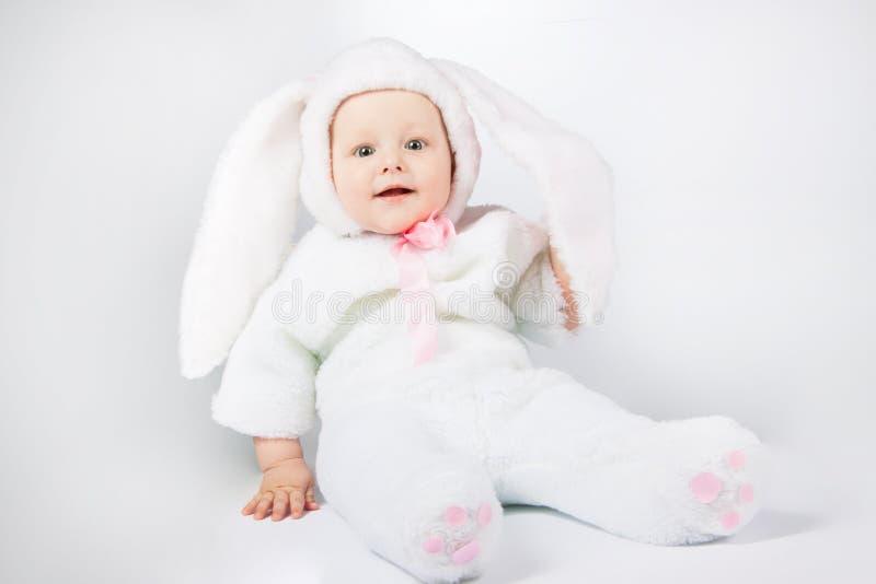 一套白色兔宝宝衣服的小逗人喜爱的婴孩 库存图片