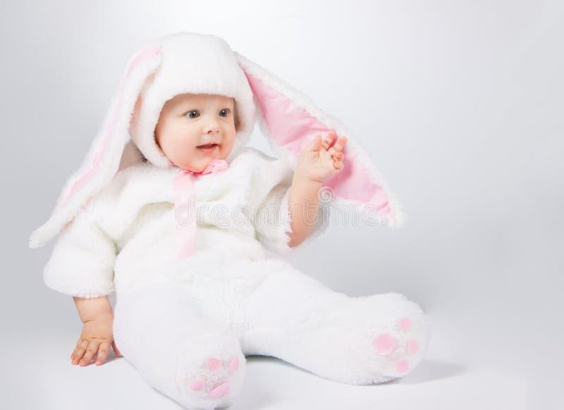 一套白色兔宝宝衣服的小逗人喜爱的婴孩 图库摄影