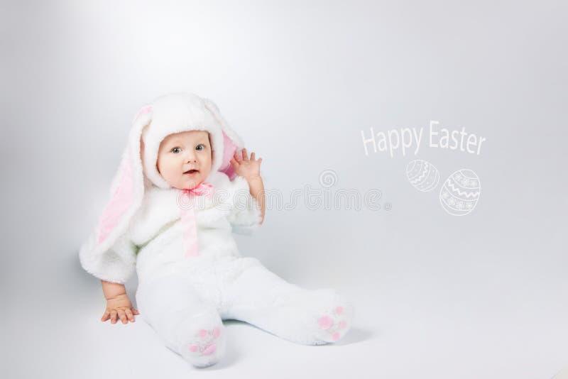 一套白色兔宝宝衣服的小逗人喜爱的婴孩 免版税库存照片