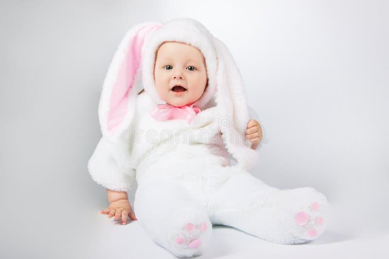 一套白色兔宝宝衣服的小逗人喜爱的婴孩 库存照片