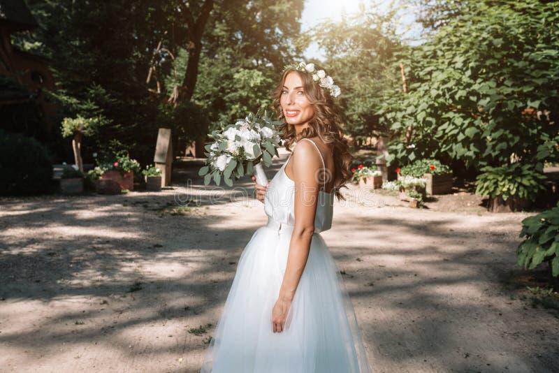 一套白色婚礼礼服的一名逗人喜爱的卷曲在她的站立回到照相机的头发的妇女与婚礼花束和花圈本质上 C 库存图片