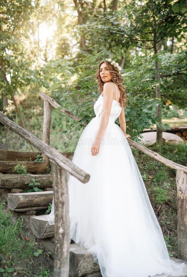 一套白色婚礼礼服的一名逗人喜爱的卷曲在她的站立回到照相机的头发的妇女与婚礼花束和花圈本质上 免版税库存图片